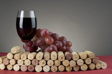 Red wine glass with grape and corks.