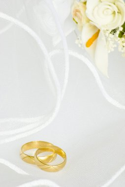 Wedding rings and flowers over veil