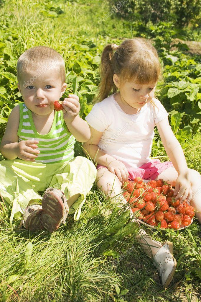 Child eating strawberries.