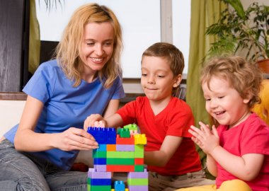 Happy mum with children plays cubes