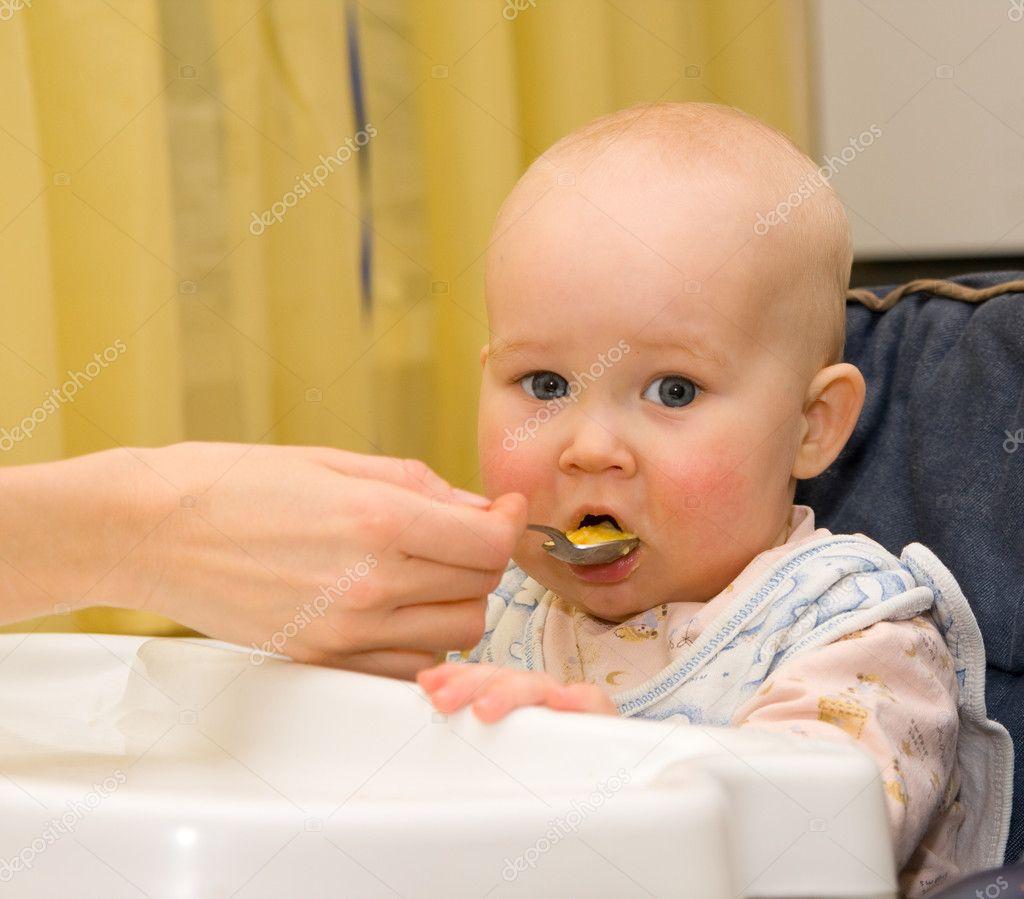 Baby eats porridge from a spoon