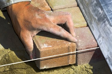 Worker puts sidewalk tile