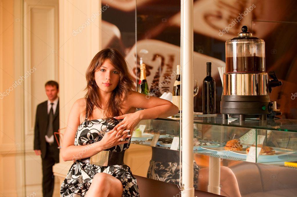 Charming girl sits at rack of bar at coffee maker.