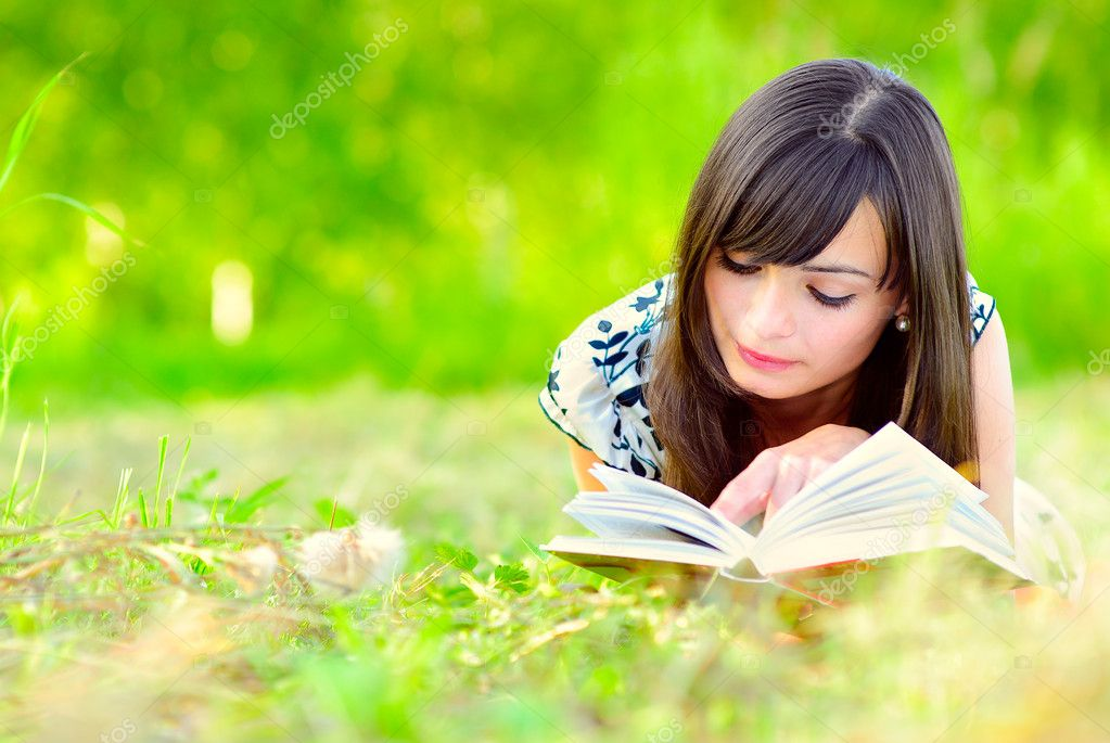 Girl reads book on meadow