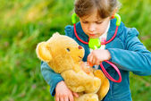 Fotografie Girl listens stethoscope to plush bear