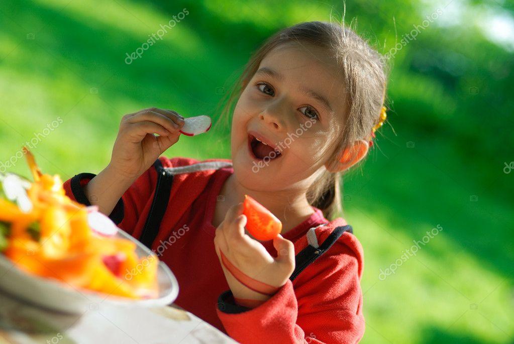 Girl eats a tomato and a garden radish