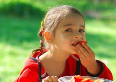 Girl bites tomato