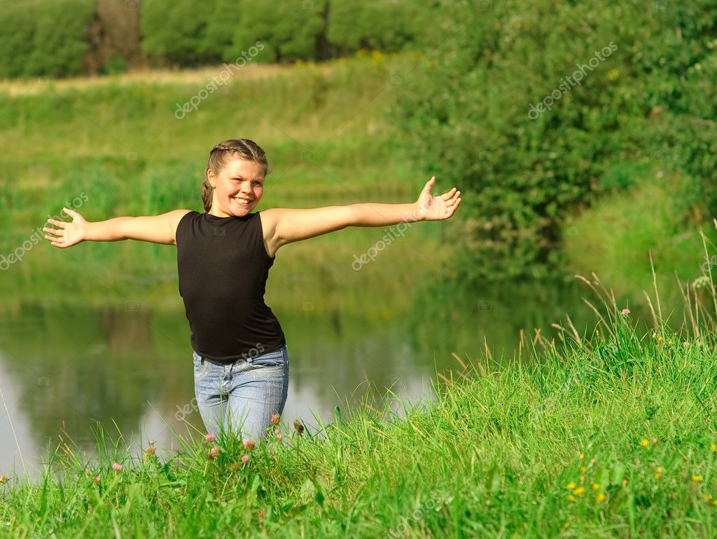 Girl has stretched hands at lake