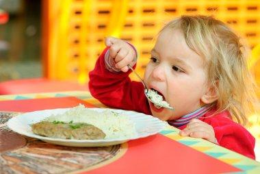 Portrait of having breakfast kid.