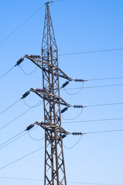 High voltage power lines over blue sky