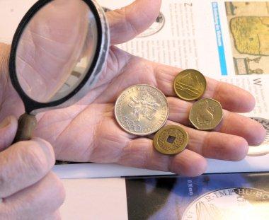 Old numismatist`s hands