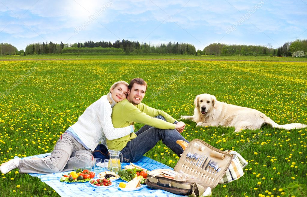 Couple at picnic with golden retriever