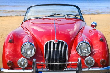 Old classic red car at the beach