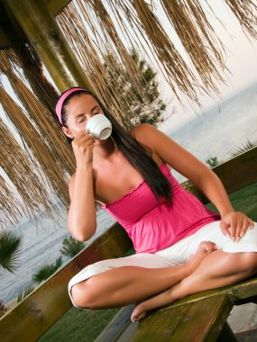 Woman having a cup of coffee in bungalow