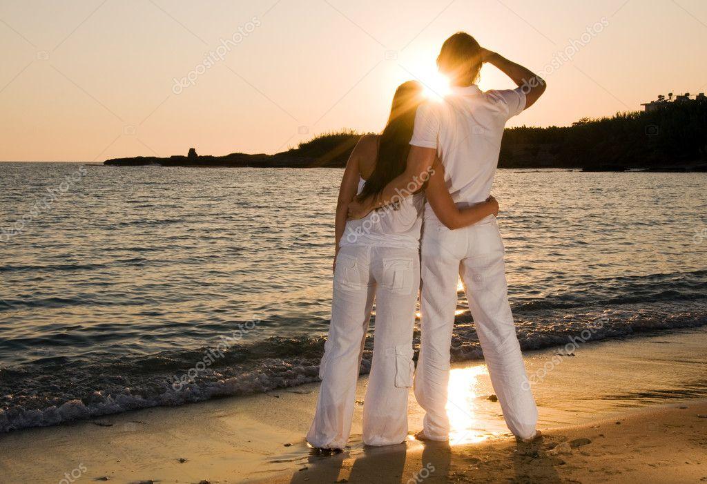 Couple hugging, enjoying summer sunset.