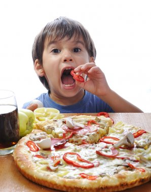 Cute little boy eating pizza on table, i