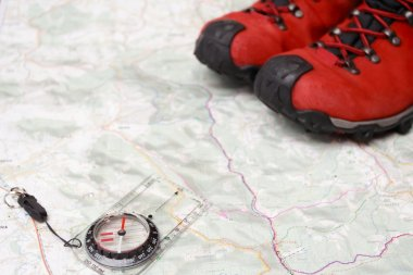 Hiking shoes and compass on map