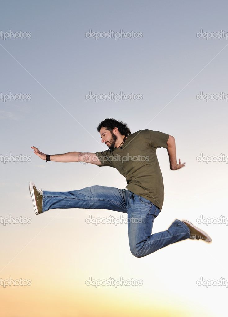 Young man jumping in air at sunset outdoor