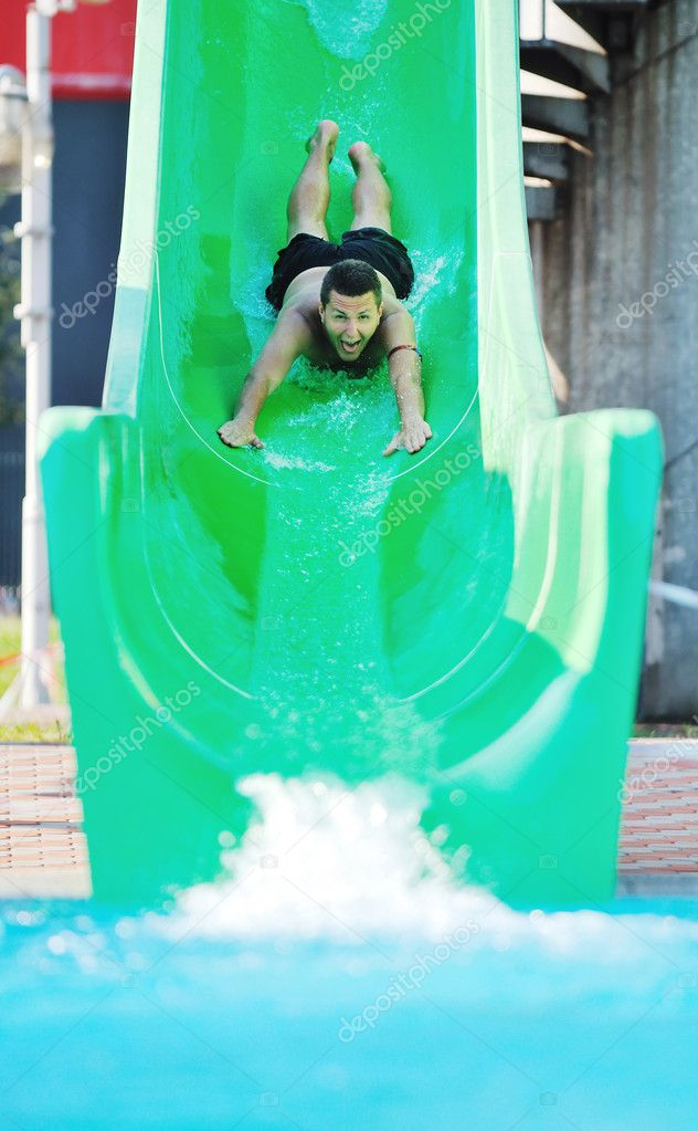 Girl have fun on water slide at outdoor swimmin