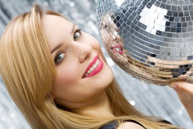 Woman with disco ball over silver backg