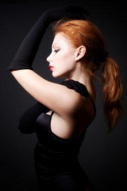 Attractive redhead model posing on dark