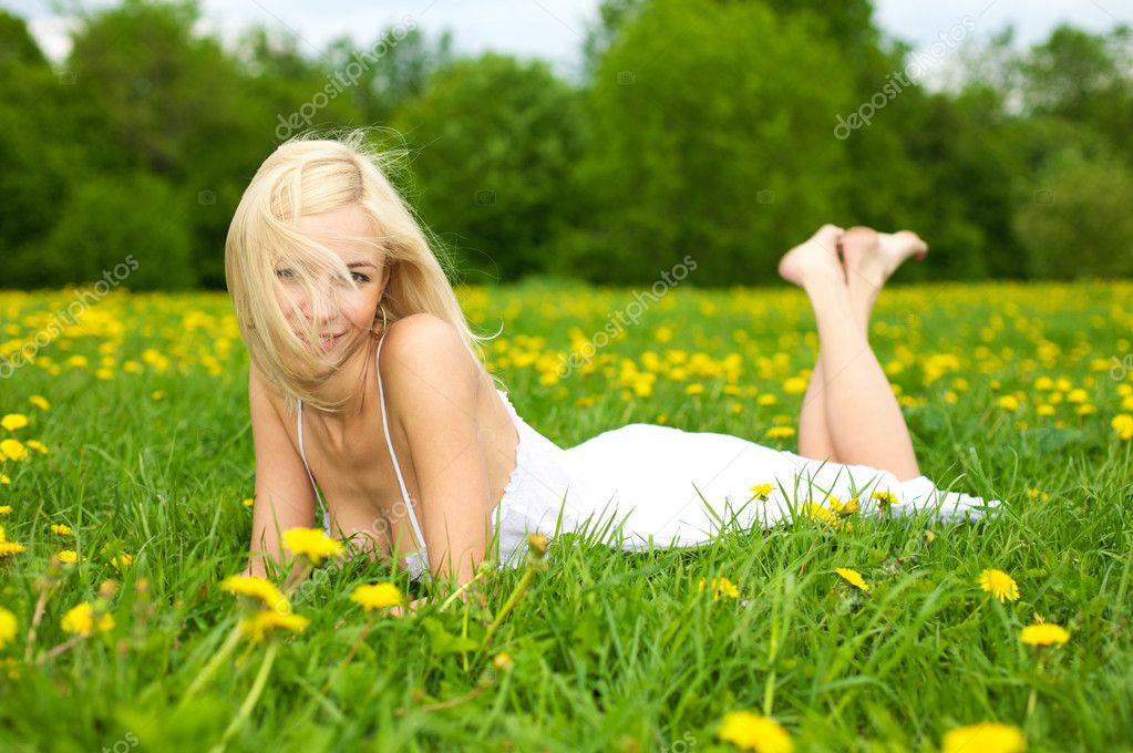 Young woman relaxing on a green meadow w