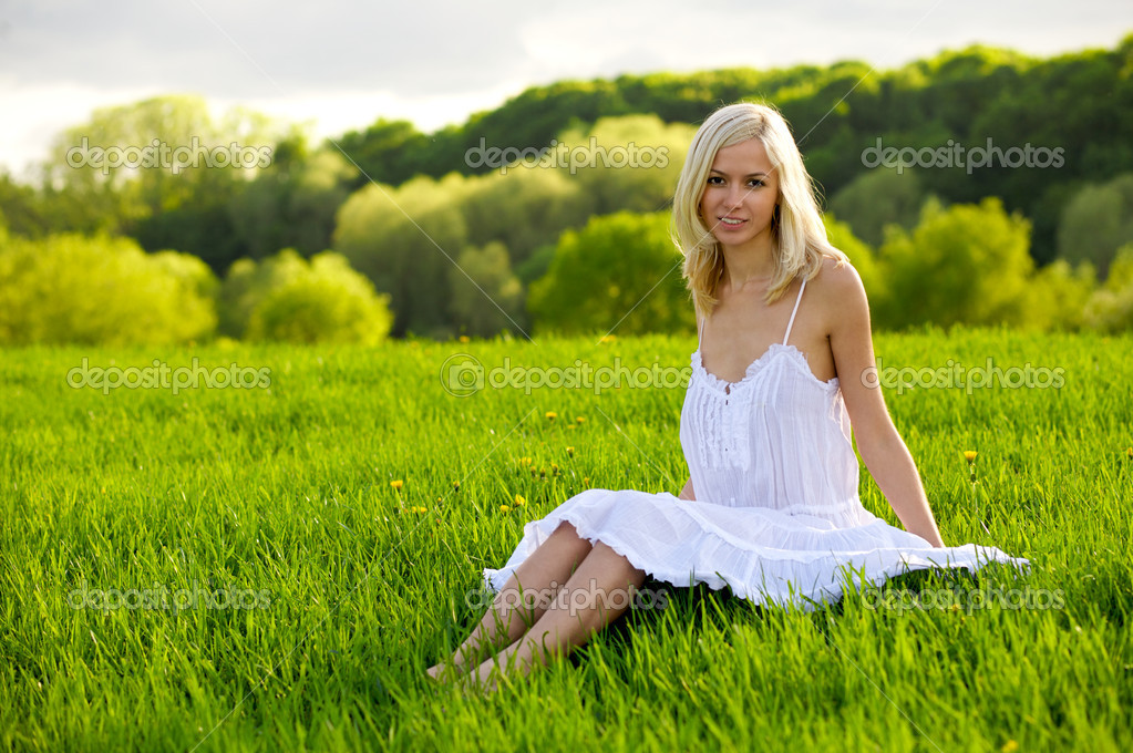 Young woman sitting on a green grass