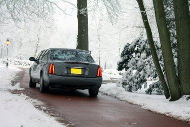 Grey limousine on a winter road