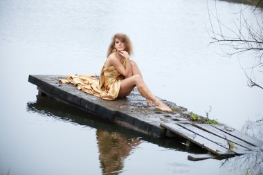 Young woman on the autumn lake