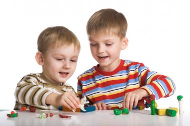 Boys mould toys from plasticine