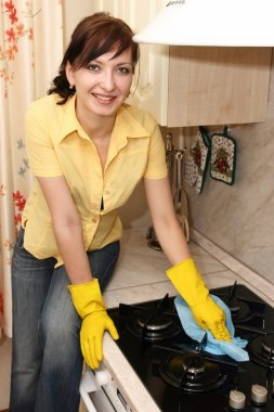 The girl on kitchen wipes a gas cooker