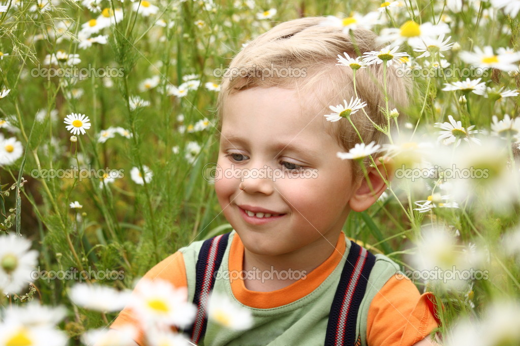 3 years boy smiling on a daisy field