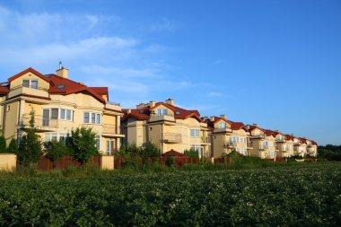 Row of similar houses over blue sky
