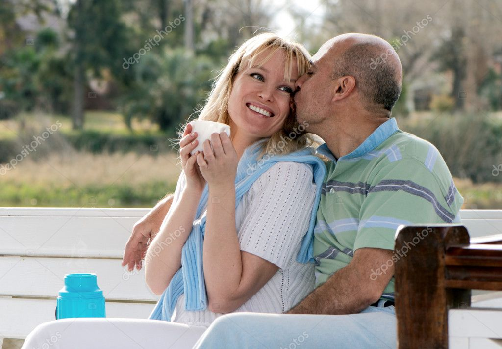 Happy couple on a bench in park
