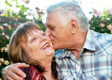 Kissing happy elderly couple in love outdoor