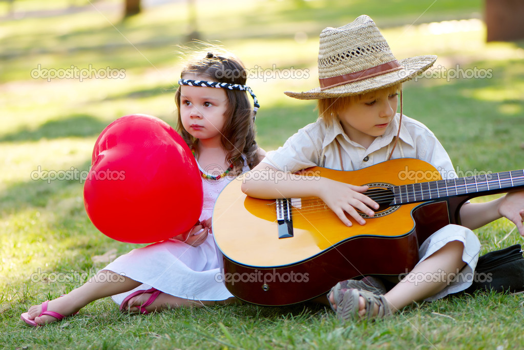 Couple with guitar on grass in park