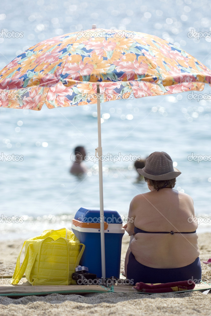 Overweight woman sitting on the beach