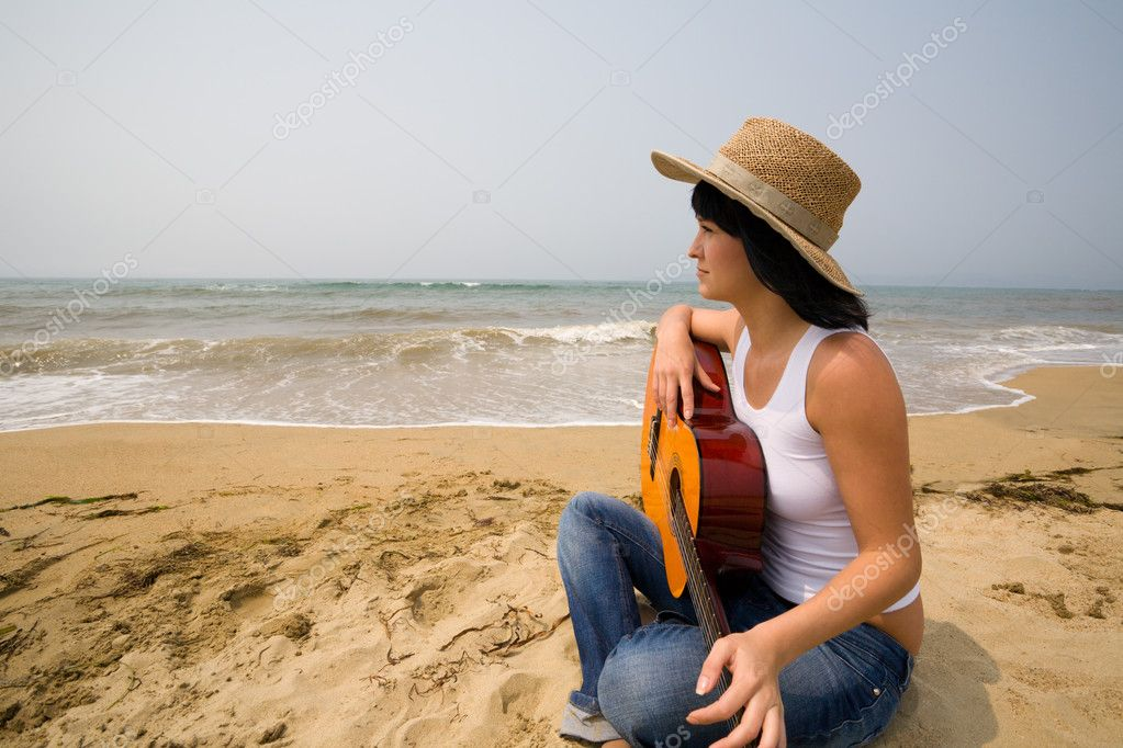 Young woman and guitar. Beach