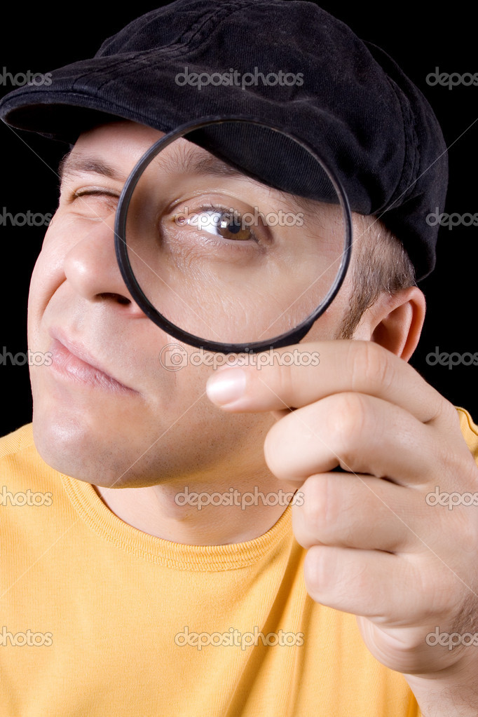 Detective with magnifying glass on black background
