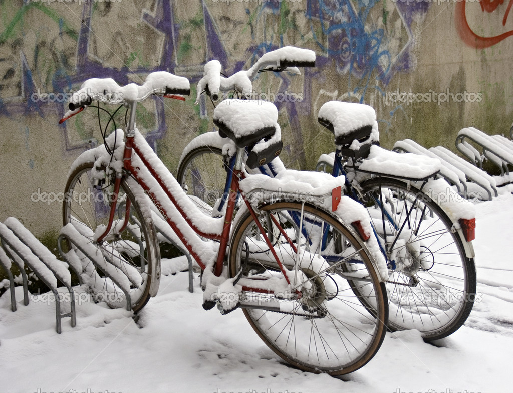 Two bikes covered with snow