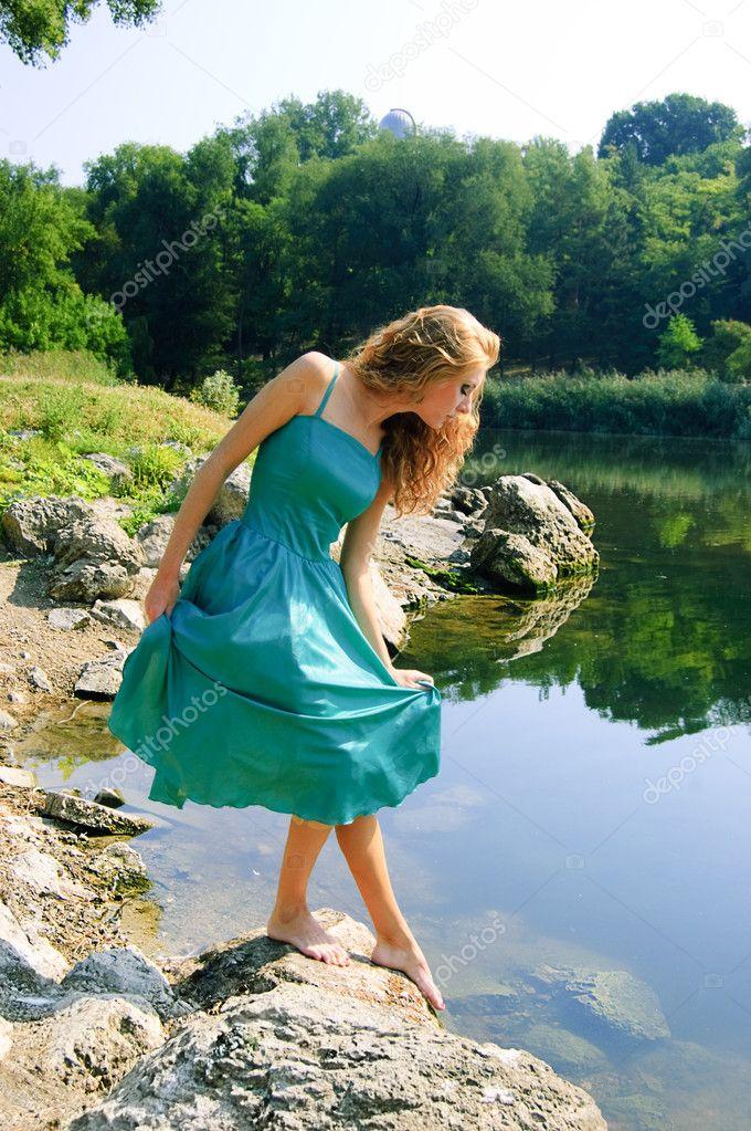 Sensual girl in dress near lake