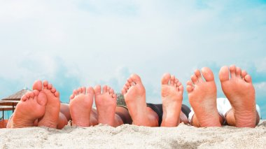 Young couples feet at the beach