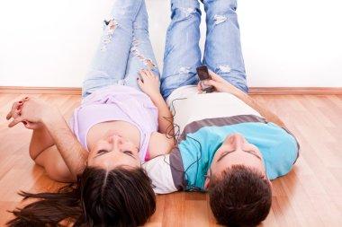 Happy couple on floor listening music