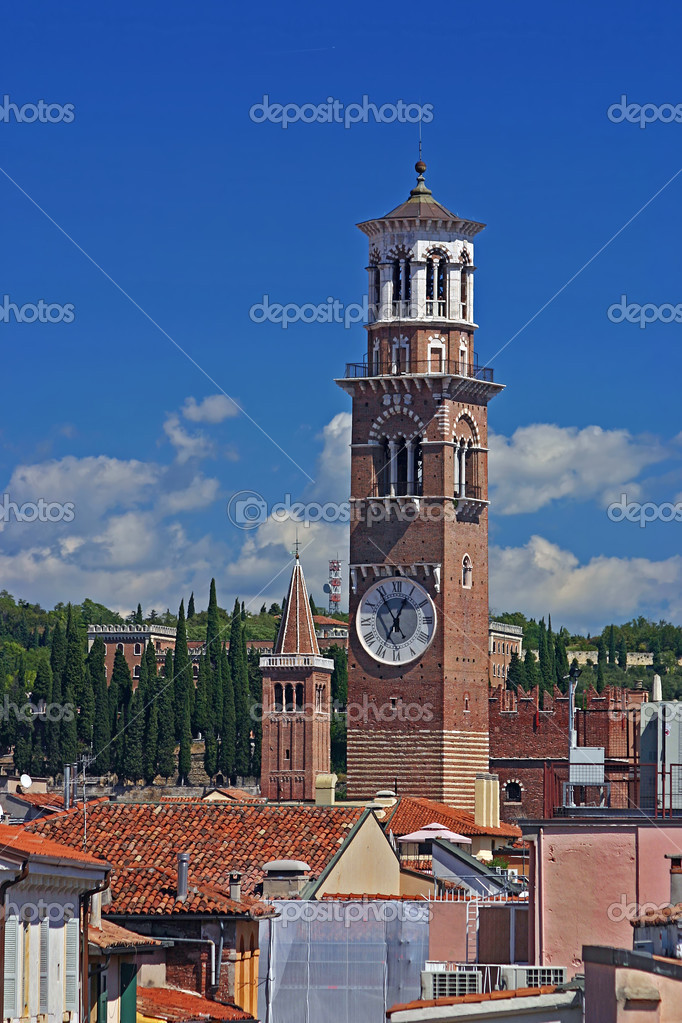 Lamberti Tower with the spire of the Church of Santa Anastasia in the background against blue sky and clouds on the skyline of Verona, Italy