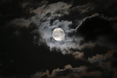 Full moon in eerie white clouds