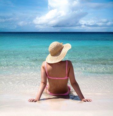 Beautiful woman sitting on seashore