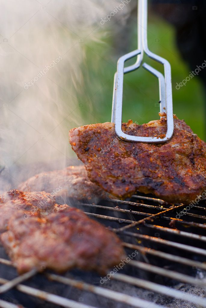 Barbecue detail with metal tongs.