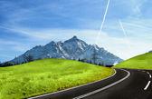 horská silnice a zasněžené Alpy