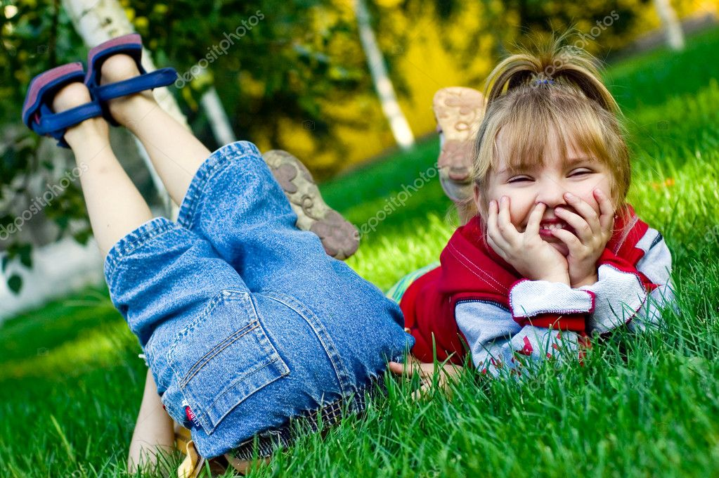 Amusing children on a green grass