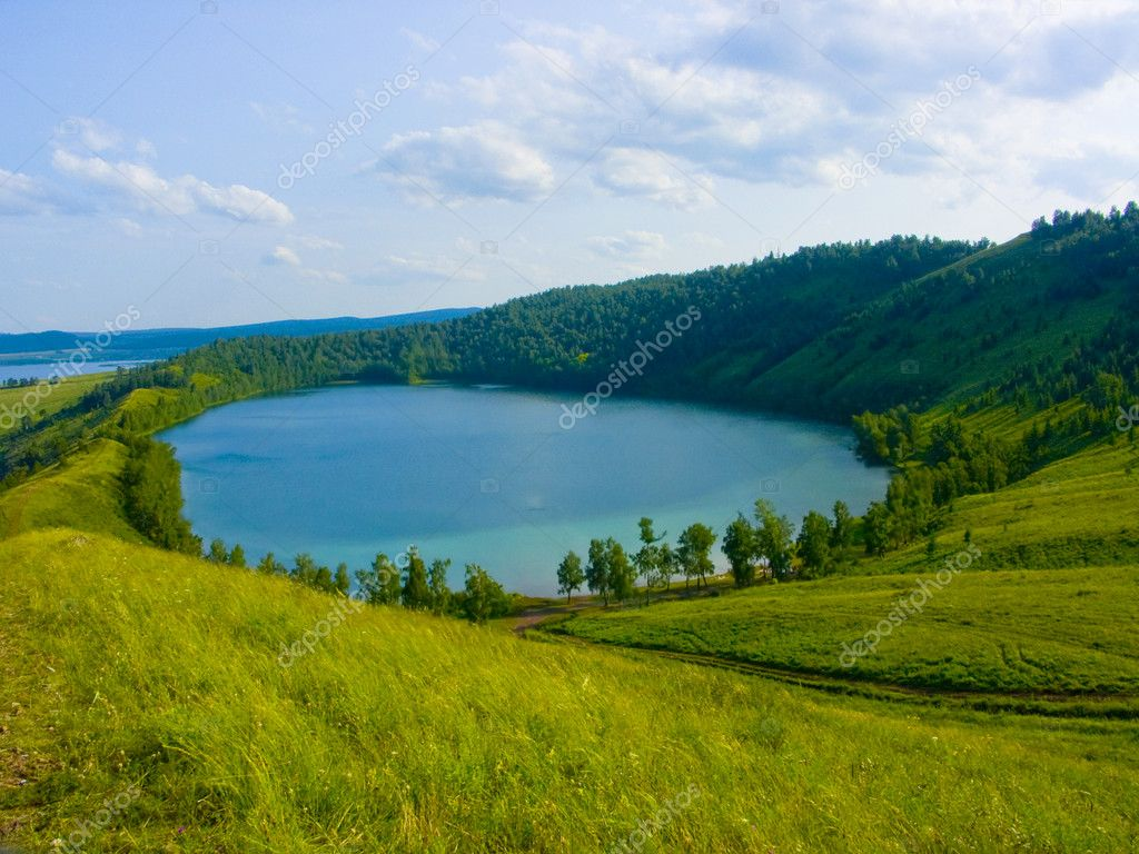 The image of the lake located in a hollow of a hill